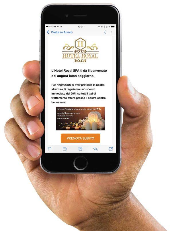 Una mano che sorregge uno smartphone iPhone su cui è visulaizzata la mail promozionale di un albergo inviata usando la funzione Engagement del software hotspot Wi-Fi Hotel.