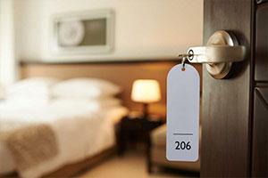 Veduta di una stanza di albergo con sistema wi-fi hotel dalla porta di entrata., con il numero della camera e la chiave in primo piano.