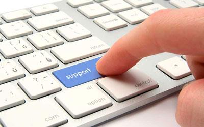 Un dito spinge un tasto blu di una tastiera sul quale c'è scritta la parola supporto.