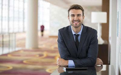 Un uomo in giacca e cravatta sorridente nella hall di un albergo.