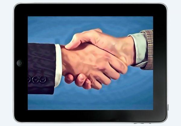 Un tablet mostra due mani che si prendono in una stretta di mano.