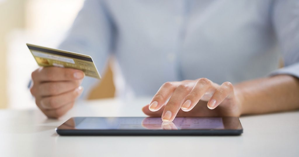 Uomo intento a effettuare un acquisto online usando una carta di credito e un tablet.