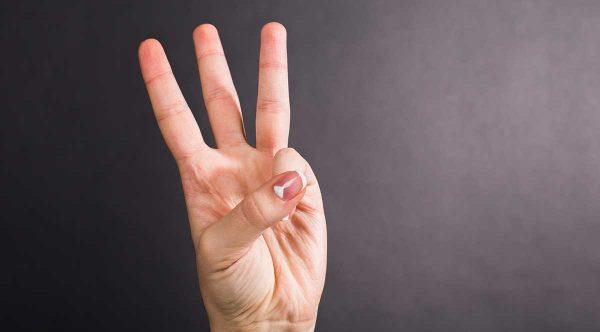 Mano aperta su tre dita che indicano il numero tre.