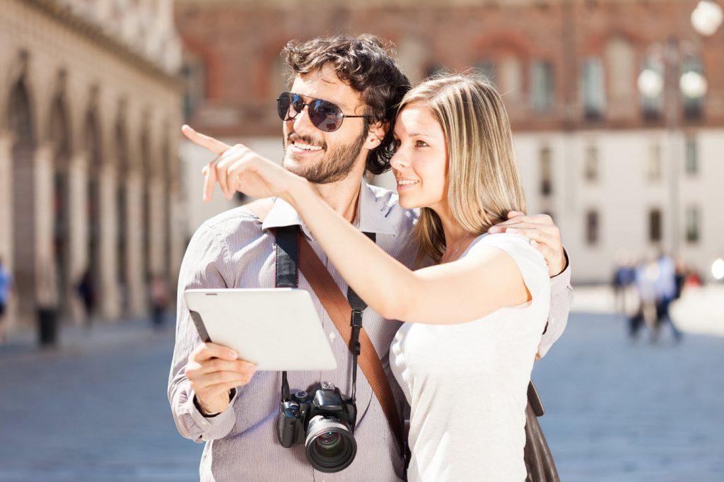 Un uomo e una donna che fanno i turisti in una piazza e osservano i luoghi orientandosi con un tablet.